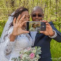 Les mariés font un selfie dans la forêt.