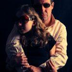 Un père et sa fille portent des lunettes de soleil et sont photographiés en studio sur fond noir.