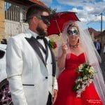 La mariée porte une ombrelle et une robe rouge. Le marié est en blanc et porte un masque tout comme sa future femme..