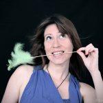 Portrait studio de jeune femme portant un plumeau dans la bouche.