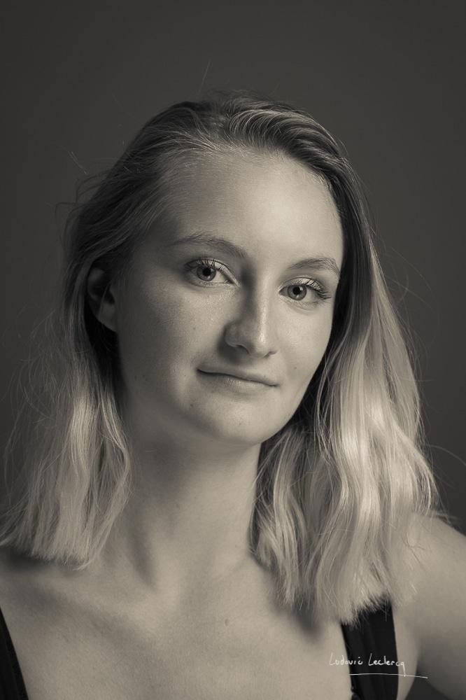Portrait studio de jeune femme blonde en noir et blanc.